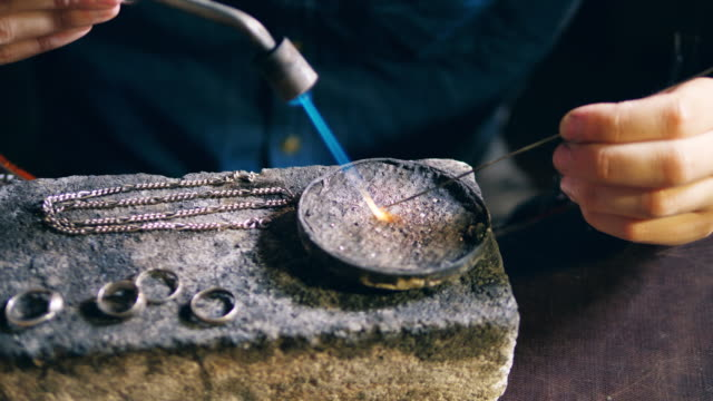 Pieces of silver jewelry are getting fixed by the goldsmith video