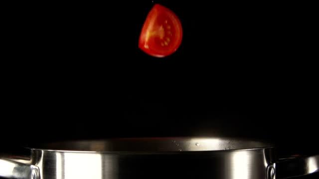 pezzi di pomodoro cadere in padella in acciaio su uno sfondo nero - chef triste video stock e b–roll