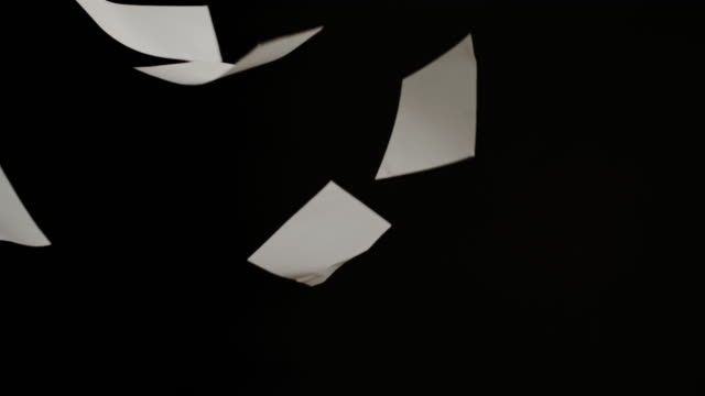 Pieces of white paper fall on a black background in slow motion.
