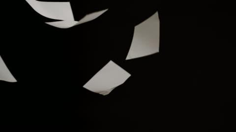 vídeos y material grabado en eventos de stock de caída de trozos de papel blanco sobre un fondo negro en cámara lenta. - papel