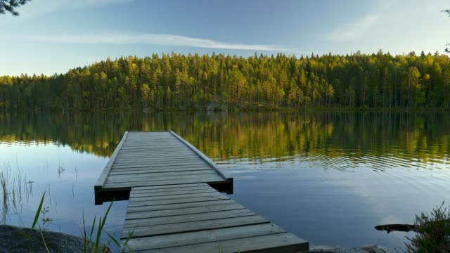 Pier in Repovesi national park, Kouvola, Finland.  Steadicam shot of pier and lake with reflections at sunset. 4K, UHD