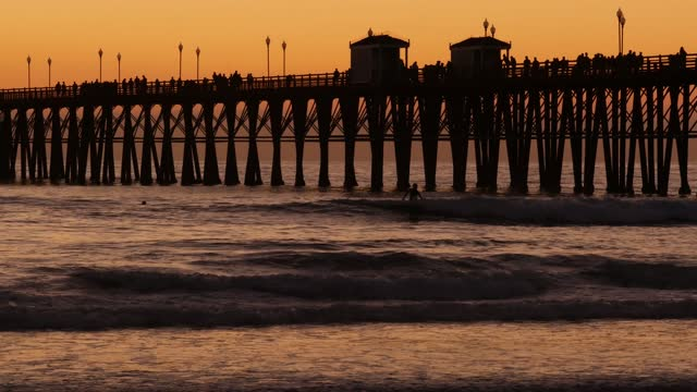 Pier silhouette at sunset, California USA, Oceanside. Surfing resort, ocean tropical beach. Surfer waiting for wave.