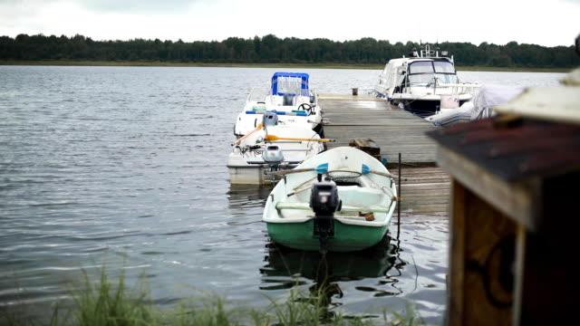 vídeos de stock e filmes b-roll de a pier with small boats is seen in the fishing village - arquipélago