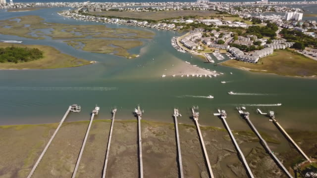Piers Over the Intracoastal Waterway An aerial view of piers jutting out into the Atlantic Intracoastal Waterway, near Wilmington, NC, USA. marsh stock videos & royalty-free footage