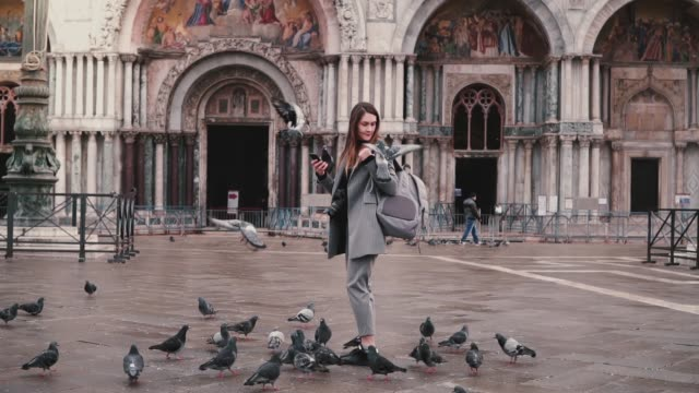 Pigeon sits on arm of beautiful female tourist with smartphone and backpack on city square in Venice, Italy slow motion.