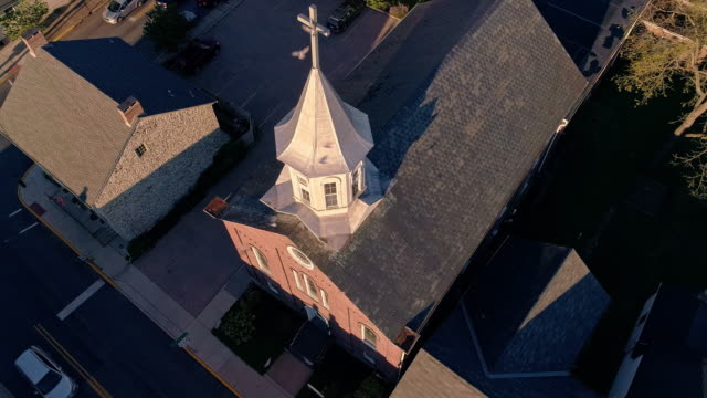 Pigeons flying over the church in Bath, a small Pennsylvanian town, at sunset. Appalachian mountains, Pennsylvania, USA. Aerial drone video with the static camera, the ascending motion. - vídeo