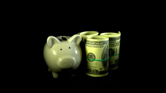 Piggy bank and dollar bills turn on a black background