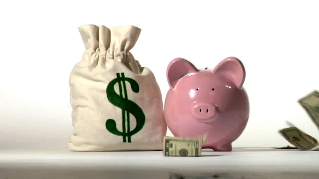 Piggy bank and falling money Piggy bank and falling money. Slow motion piggy bank stock videos & royalty-free footage