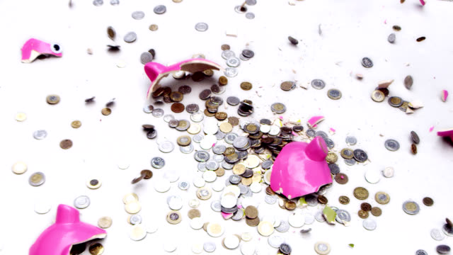 Piggy bank breaking into pieces. Slow Motion video