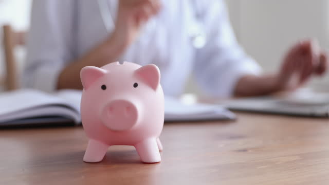piggy bank on table with female doctor working in background - risparmi video stock e b–roll