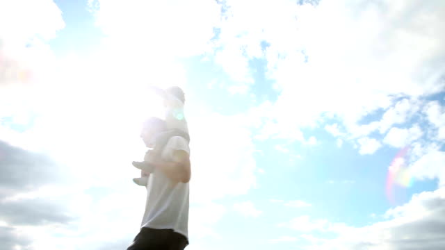 huckepack nehmen-vater sohn auf schultern tragen gegen himmel hintergrund - schulter stock-videos und b-roll-filmmaterial