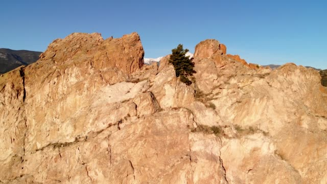 Pikes Peak reveals from behind Garden of the Gods drone fly up shot.
