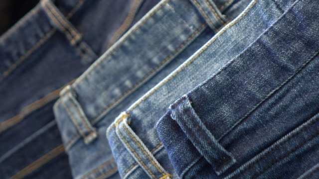 pile of blue and black jeans - jeans video stock e b–roll