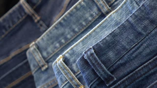 pile of blue and black jeans - dżinsy filmów i materiałów b-roll