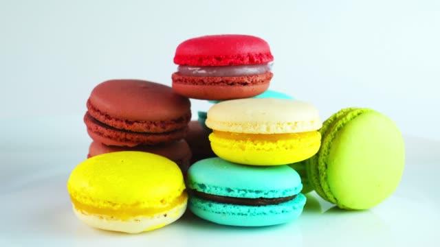 pile of colorful macaroons on white background - francuska kuchnia filmów i materiałów b-roll