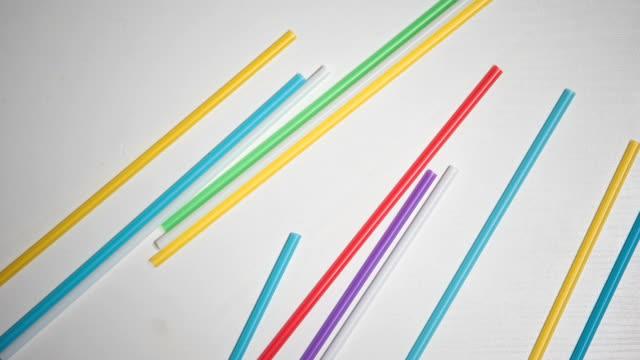 pila di cannucce di plastica colorate su sfondo bianco, inquinamento ambientale - paglia video stock e b–roll