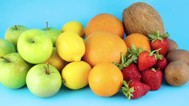 pile of different fresh organic fruits on blue background. oranges, apples, kiwi, strawberries, lemons and coconut - icon set healthy video stock e b–roll
