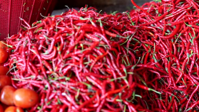 vídeos y material grabado en eventos de stock de pila de chiles calientes frescos en el mercado tradicional - cayena guindilla roja