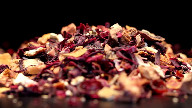 pile of fruit tea with petals and dry fruit isolated on black - naturopathy stock videos and b-roll footage