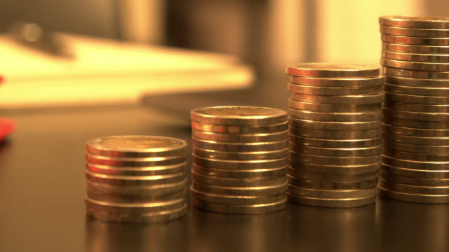 pile of golden coins on the work desk - guadagnare soldi video stock e b–roll