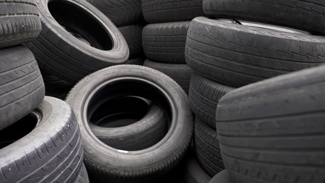 Pile of old vehicle tires in warehouse.