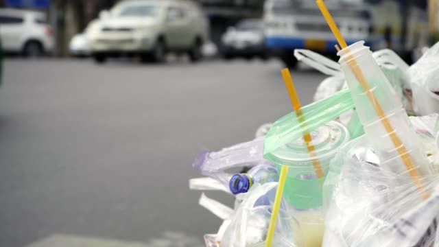 a pile of plastic waste in a garbage bin besides the road - paglia video stock e b–roll