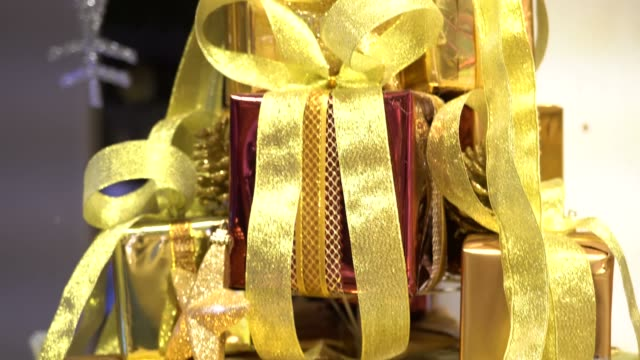 vídeos de stock e filmes b-roll de pile of present gift boxes wrapped in golden shiny paper in holiday celebration festival such as christmas time - gift box