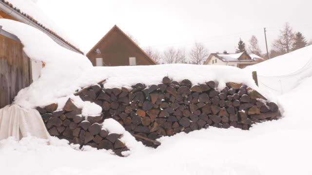 köy evi dışında kar kaplı yangın kütükleri yığını - şömine odunu stok videoları ve detay görüntü çekimi