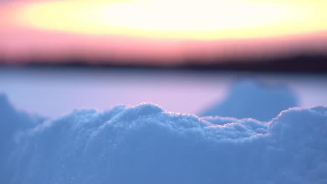 被写し界深度: 夜明け冬の荒野で雪原に輝く雪の山 ビデオ
