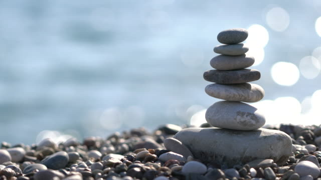 pile of stones at the beach - pietra roccia video stock e b–roll