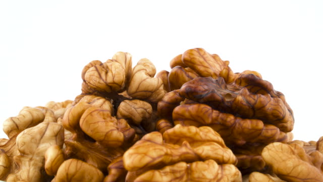Pile of walnuts without the shell. Rotating on the turntable isolated on the white background. Close up. Macro.