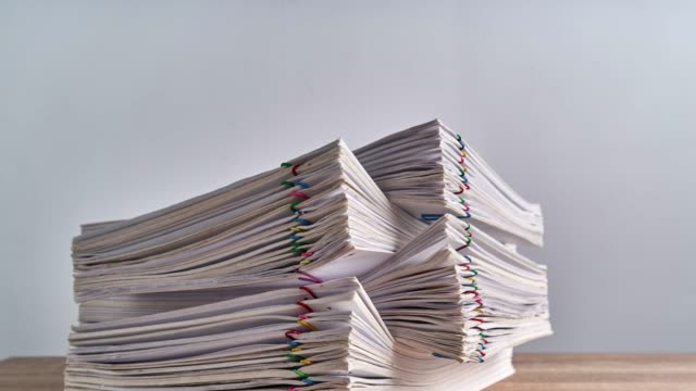 Pile overload paperwork of report on wood table time lapse