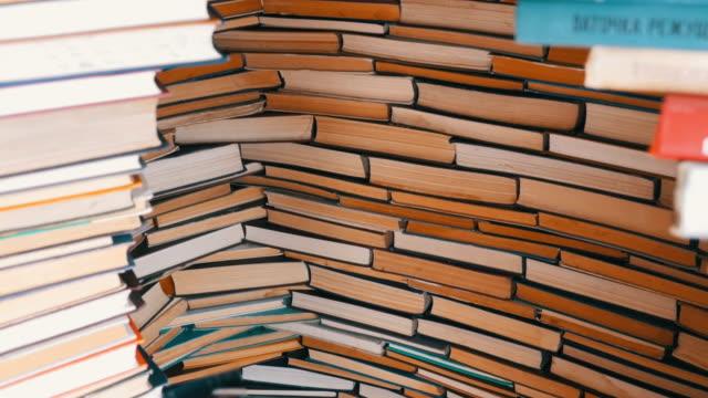 stockvideo's en b-roll-footage met stapels boeken prachtig gestapeld in een rij - boekenkast