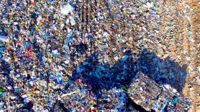 Piles of empty bottles, bags and other plastic in the garbage dump. Aerial. video