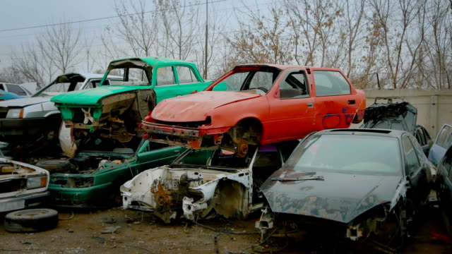 Piles of old broken rusty cars on wrecking yard video