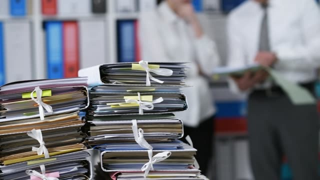 Piles of paperwork in the office and business people discussing video