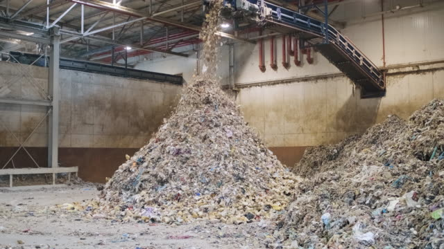 Piles of Separated Recyclables Inside Waste Facility Floor-level action shot of separated recyclables falling from elevated conveyor belt onto growing pile inside waste management facility. recycling stock videos & royalty-free footage