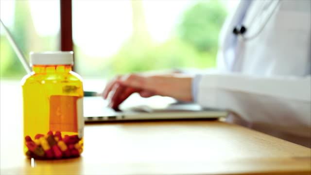 薬びん、医師でラップトップコンピュータを使う女性 - レポートのビデオ点の映像素材/bロール