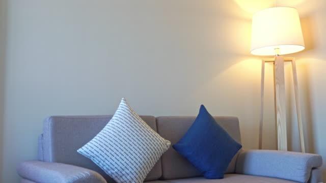 vídeos de stock e filmes b-roll de pillow on sofa with electric light lamp decoration interior of living room - living room background