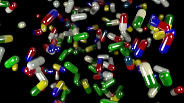 Pills drugs capsules falling slow motion closeup DOF loop video