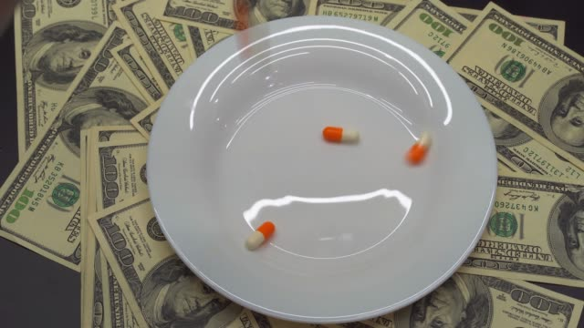 Pills fall on a plate, it costs a dollar paper money.