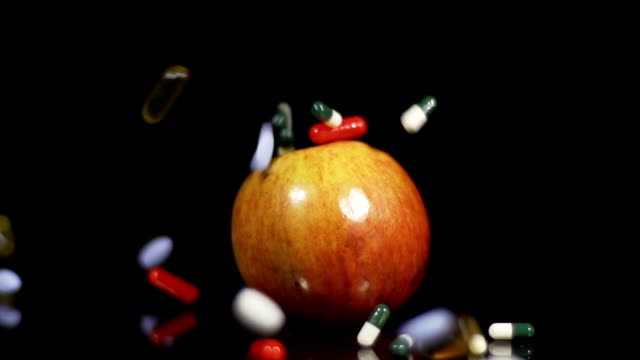 HD SLOW MOTION: Pills Falling Over An Apple video