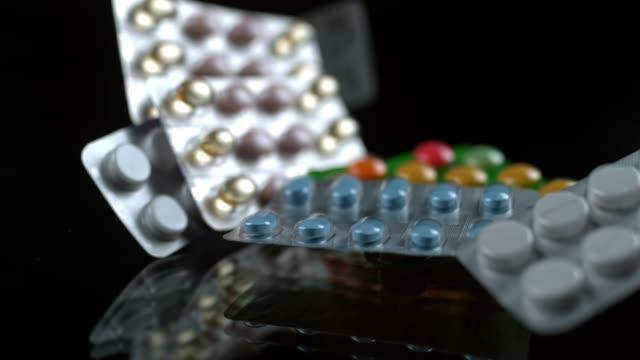 slo mo pills in blisterpackungen, die auf eine schwarze oberfläche fallen - familienplanung stock-videos und b-roll-filmmaterial