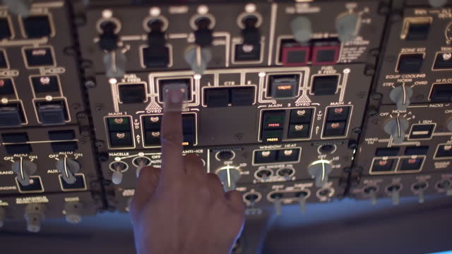 Pilot adjusting overhead controls in a cockpit video