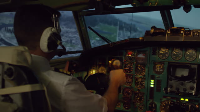 Pilot Controlling Airplane Flying over City