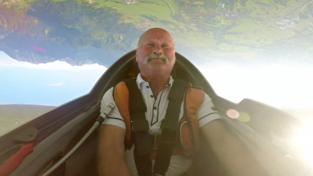ld pilot enjoying the upside down position in his glider above the sunny countryside - pilota video stock e b–roll