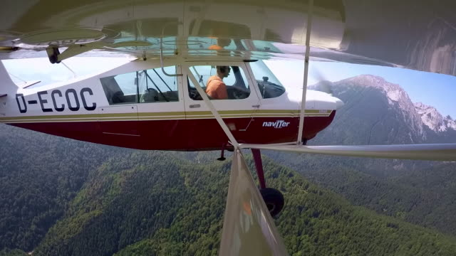 LD Pilot flying a light aircraft above a forest in sunshine Wide locked down shot of a pilot sitting in the cockpit and flying his light aircraft above a forest on a sunny day. Shot in Slovenia. private airplane stock videos & royalty-free footage
