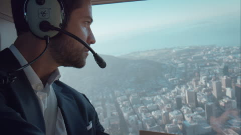Pilot flying helicopter Pilot flying helicopter. He is wearing headphones and flys over a city. helicopter stock videos & royalty-free footage