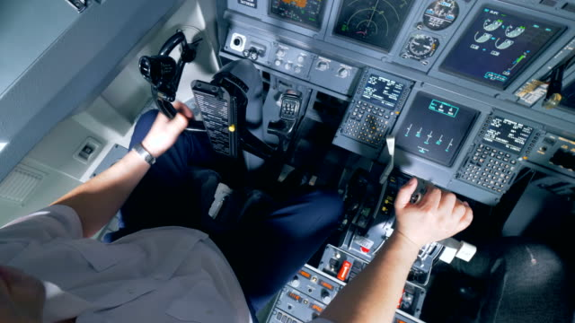 a pilot holds his hand on the lever in a cockpit, close up. - leva video stock e b–roll
