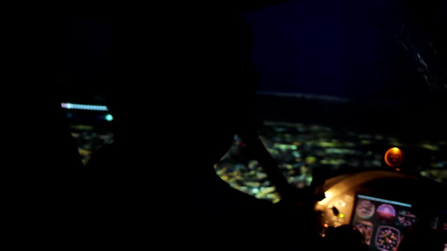 Pilot in headset maneuvering airplane above evening city, responsible job video